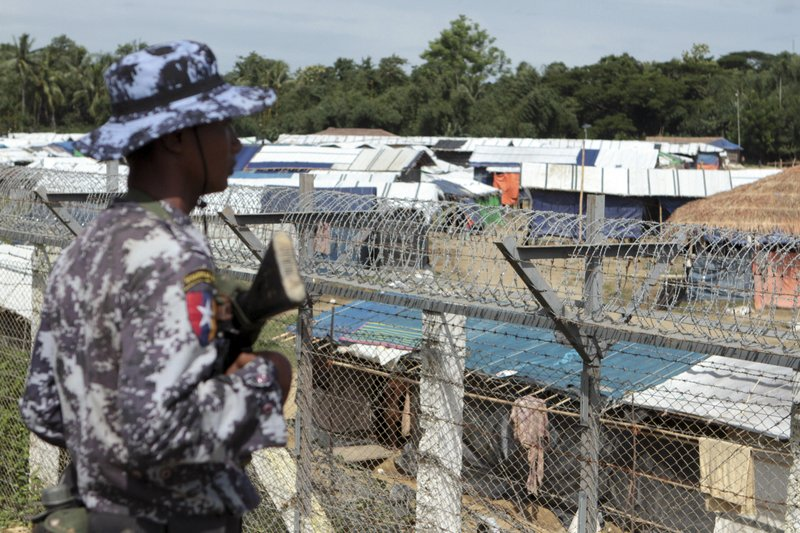 FILE - In this June 29, 2018, file photo, a Myanmar border guard stands to provide security near a fence at a no-man's land between Myanmar and Bangladesh, near Taungpyolatyar village, Maung Daw, northern Rakhine State, Myanmar. (AP Photo/Min Kyi Thein, File)