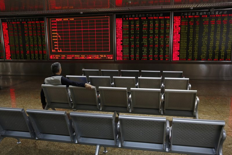 A man sits alone on a bench monitors stock prices at a brokerage house in Beijing, Tuesday, May 14, 2019. (AP Photo/Andy Wong)