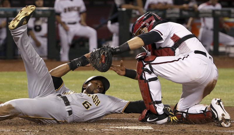 Pittsburgh Pirates' Starling Marte (6) is tagged out by Arizona Diamondbacks catcher Alex Avila, right,  while trying to score a run during the fifth inning of a baseball game Monday, May 13, 2019, in Phoenix. (AP Photo/Ross D. Franklin)