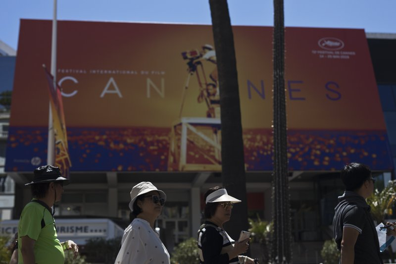 Festival goers walk by the Palais des festivals during the 72nd international film festival, Cannes, southern France, Monday, May 13, 2019. (AP Photo/Petros Giannakouris)