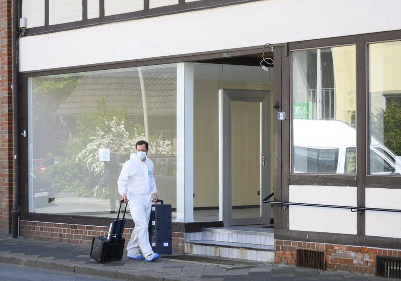 A crime scene officer arrives a crime scene where the bodies of two women have been found at an apartment in Wittingen, northern Germany, Monday, May 13, 2019. (Christophe Gateau/dpa via AP)