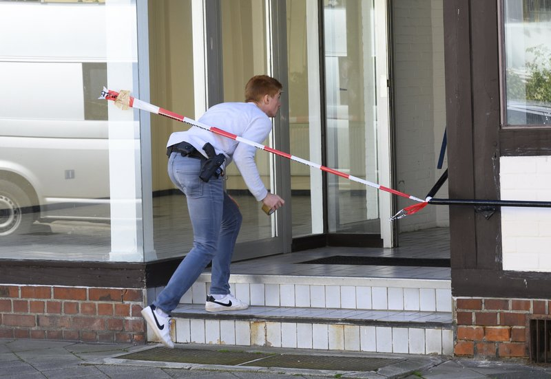 A police officer arrives at a building where the bodies of two women have been found at an apartment in Wittlingen, northern Germany, Monday, May 13, 2019. (Christophe Gateau/dpa via AP)