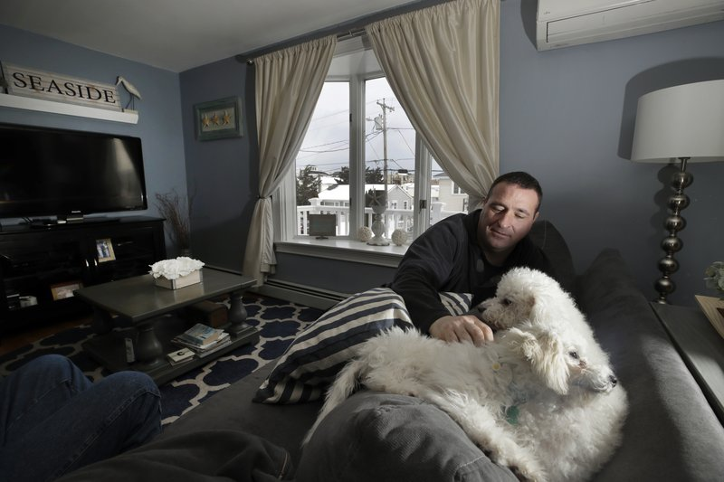 In this Jan. 23, 2019 photo, Denis Champagne, Jr. plays with his dogs Maebelle and Isabel at home near the coast in Salisbury, Mass. (AP Photo/Elise Amendola)