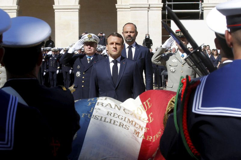 French President Emmanuel Macron honors the late special forces soldiers Cedric de Pierrepont and Alain Bertoncello, who were killed in a night-time rescue of four foreign hostages including two French citizens in Burkina Faso last week, during a national tribute at the Invalides, in Paris, Tuesday, May 14, 2019. (Philippe Wojazer/Pool via AP)