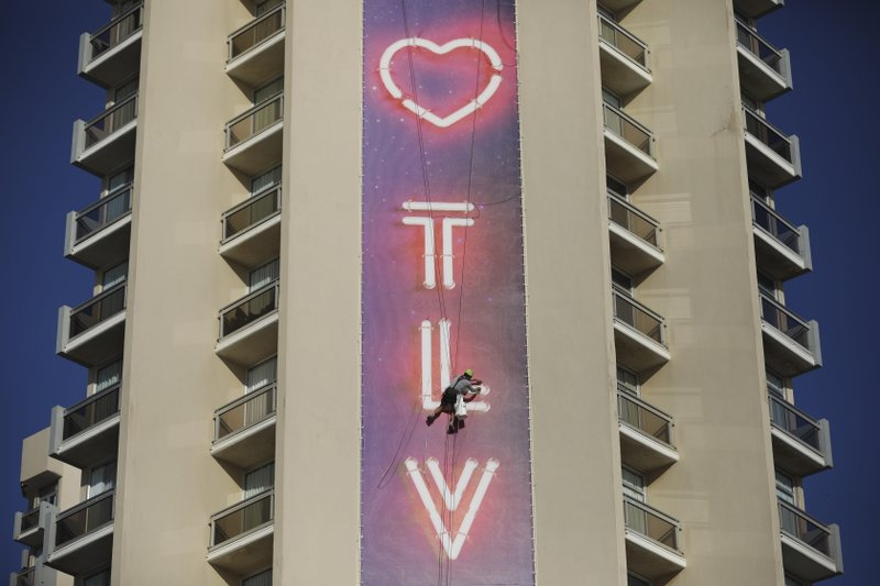 A man works on a Eurovision Song Contest banner on a building in Tel Aviv, Monday, May 13, 2019. (AP Photo/Oded Balilty)