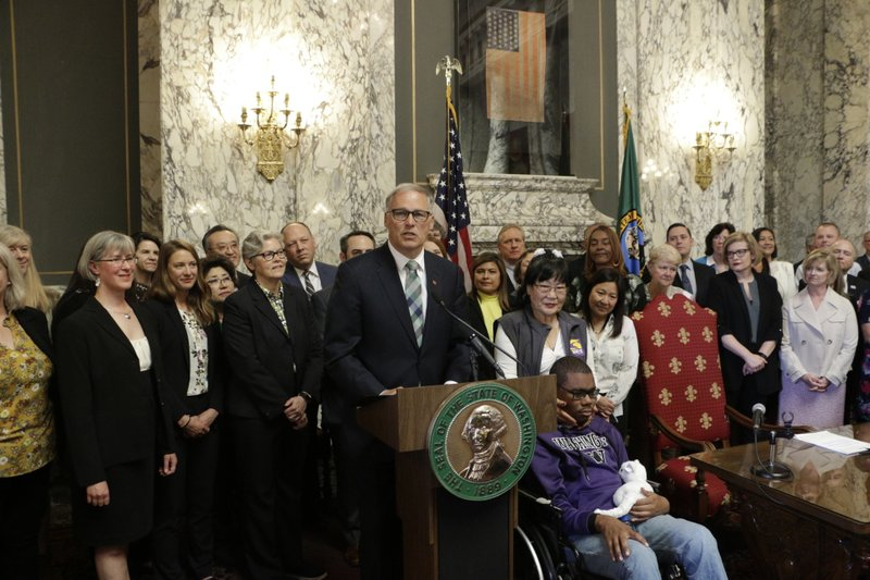 Gov. Jay Inslee, at podium, speaks before signing a measure that makes Washington the first state in the nation to establish a program to help offset the costs of long-term care, Monday, May 13, 2019, in Olympia, Wash. (AP Photo/Rachel La Corte)