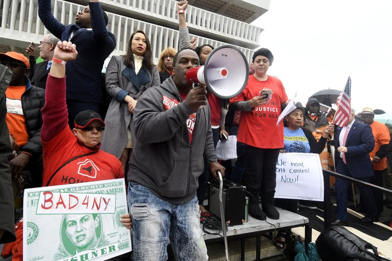 Wayne Benson of Albany, N.Y., stands with tenants and elected officials urging New York Gov. Andrew Cuomo and state legislators to pass universal rent control legislation that would strengthen and expand tenants rights across the state of New York before rent laws expire next month during a rally at the state Capitol Tuesday, May 14, 2019, in Albany, N. (AP Photo/Hans Pennink)