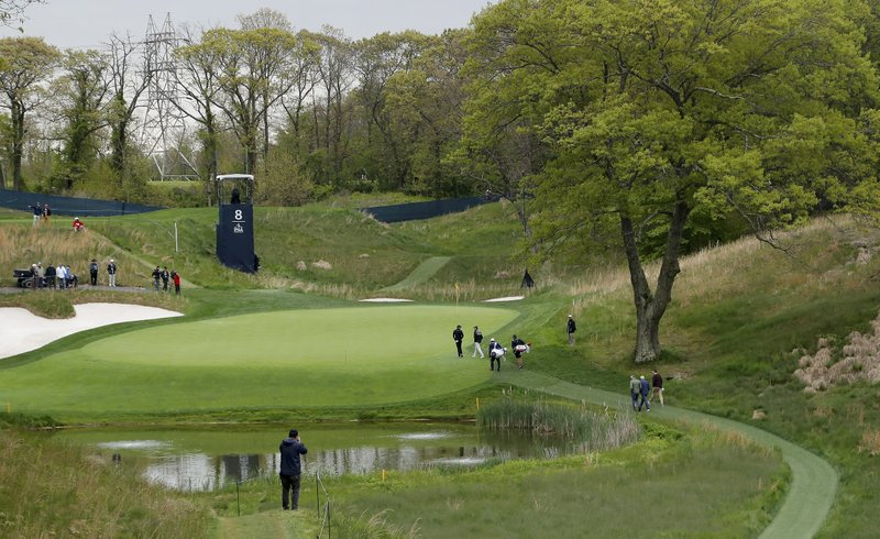Rory McIlroy, center left, and Russell Knox walk onto the eighth green during a practice round for the PGA Championship golf tournament, Tuesday, May 14, 2019, in Farmingdale, N. (AP Photo/Julie Jacobson)