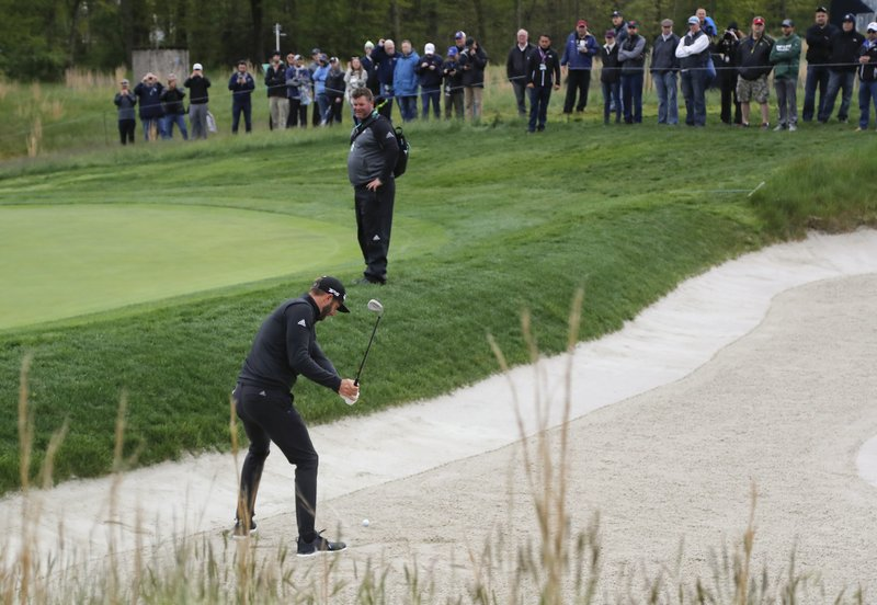 Dustin Johnson hits out of a bunker on the fifth hole during a practice round at the PGA Championship golf tournament, Tuesday, May 14, 2019, in Farmingdale, N. (AP Photo/Julie Jacobson)