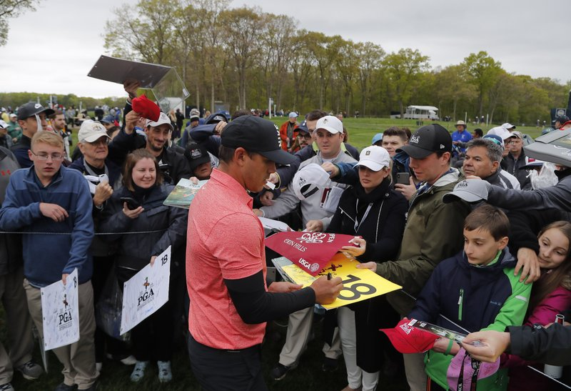 Brooks Koepka signs autographs for fans after a practice round at the PGA Championship golf tournament, Tuesday, May 14, 2019, at Bethpage Black in Farmingdale, N. (AP Photo/Julie Jacobson)