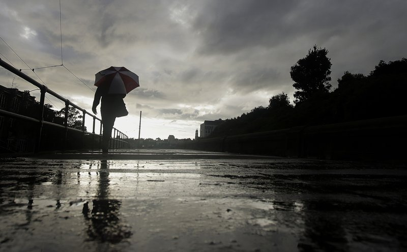 File - In this March 5, 2019, file photo, a man walks with an umbrella in the rain in San Francisco. A cold front traveling down to Northern California from the Gulf of Alaska is expected to dump at least a foot of snow in higher elevations of the Sierra Nevada weeks before the start of summer. (AP Photo/Jeff Chiu, File)