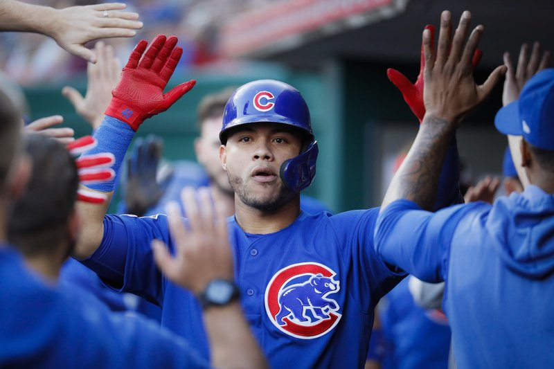 Chicago Cubs' Willson Contreras is congratulated in the dugout after hitting an RBI sacrifice fly off Cincinnati Reds starting pitcher Tanner Roark during the fifth inning of a baseball game Tuesday, May 14, 2019, in Cincinnati. (AP Photo/John Minchillo)