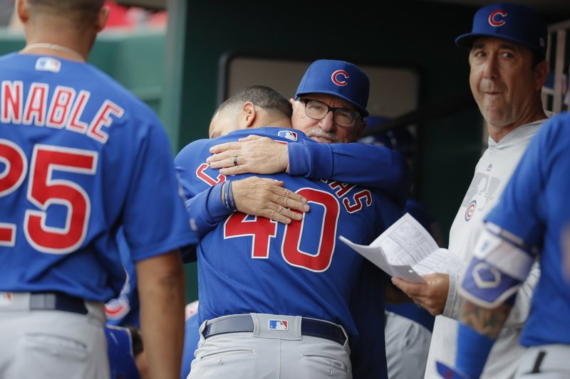 Chicago Cubs manager Joe Maddon, center right, hugs catcher Willson Contreras (40) before the team's baseball game against the Cincinnati Reds, Tuesday, May 14, 2019, in Cincinnati. (AP Photo/John Minchillo)