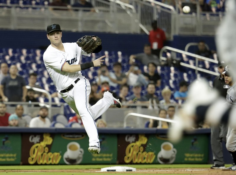 Miami Marlins third baseman Brian Anderson throws to first where Tampa Bay Rays' Avisail Garcia was safe with a RBI single in the ninth inning during a baseball game, Tuesday, May 14, 2019, in Miami. (AP Photo/Lynne Sladky)