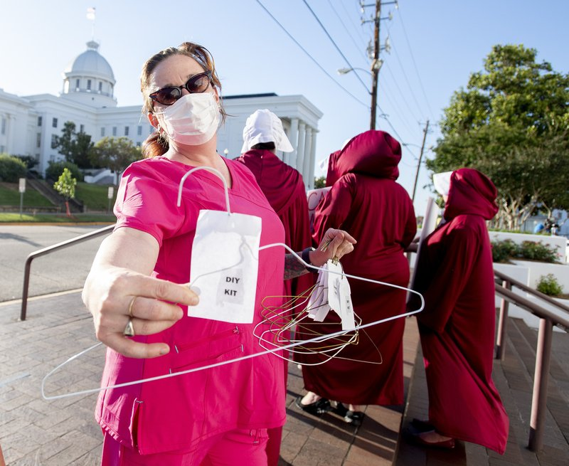 Laura Stiller hands out coat hangers as she talks about illegal abortions during a rally against HB314, the near-total ban on abortion bill, outside of the Alabama State House in Montgomery, Ala. (Mickey Welsh/The Montgomery Advertiser via AP)