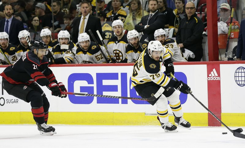 Boston Bruins' Connor Clifton controls the puck while Carolina Hurricanes' Nino Niederreiter (21), of Switzerland, defends during the first period in Game 3 of the NHL hockey Stanley Cup Eastern Conference final series in Raleigh, N. (AP Photo/Gerry Broome)