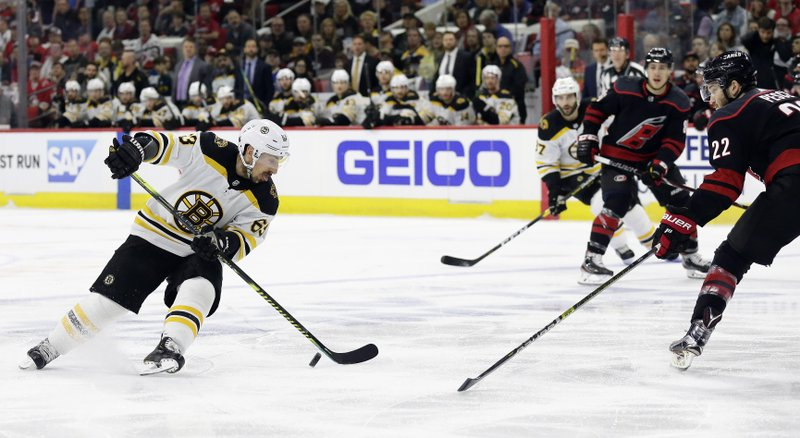 Boston Bruins' Brad Marchand (63) controls the puck against Carolina Hurricanes' Brett Pesce (22) during the first period in Game 3 of the NHL hockey Stanley Cup Eastern Conference final series in Raleigh, N. (AP Photo/Gerry Broome)