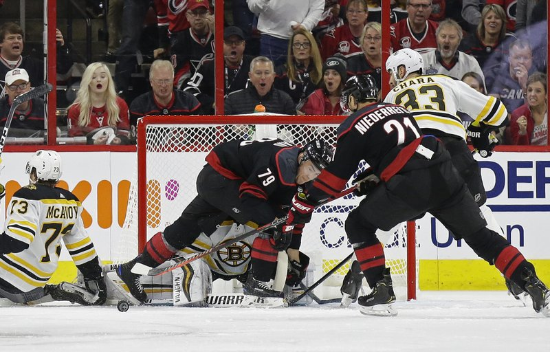 Carolina Hurricanes' Micheal Ferland (79) and Nino Niederreiter (21), of Switzerland, try to score against Boston Bruins goalie Tuukka Rask (40), of Finland, while Bruins' Zdeno Chara (33), of Slovakia, and Charlie McAvoy (73) defend during the first period in Game 3 of the NHL hockey Stanley Cup Eastern Conference final series in Raleigh, N. (AP Photo/Gerry Broome)