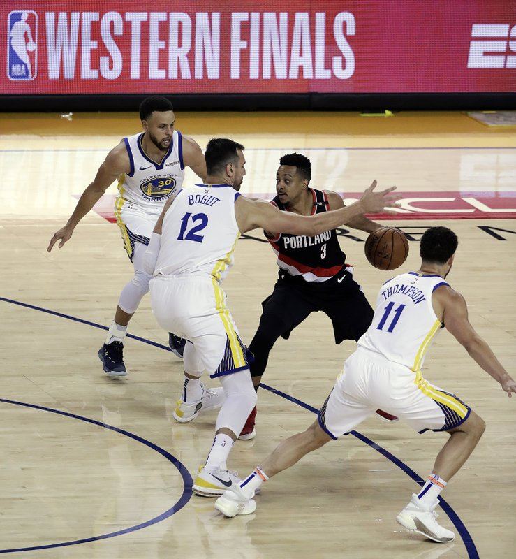 Portland Trail Blazers' CJ McCollum (3) drives the ball against Golden State Warriors' Andrew Bogut (12), Stephen Curry, left, and Klay Thompson (11) during the first half of Game 1 of the NBA basketball playoffs Western Conference finals Tuesday, May 14, 2019, in Oakland, Calif. (AP Photo/Jeff Chiu)
