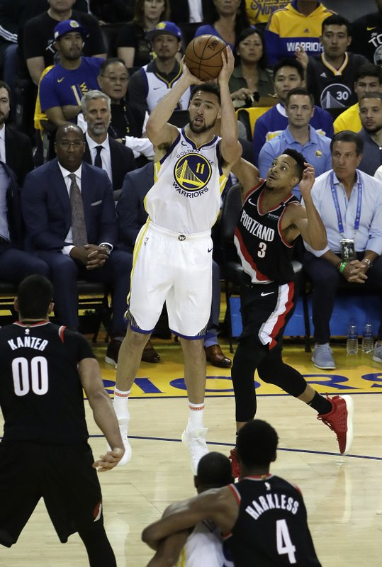 Golden State Warriors' Klay Thompson (11) shoots past Portland Trail Blazers' CJ McCollum (3) during the first quarter of Game 1 of the NBA basketball playoffs Western Conference finals Tuesday, May 14, 2019, in Oakland, Calif. (AP Photo/Jeff Chiu)