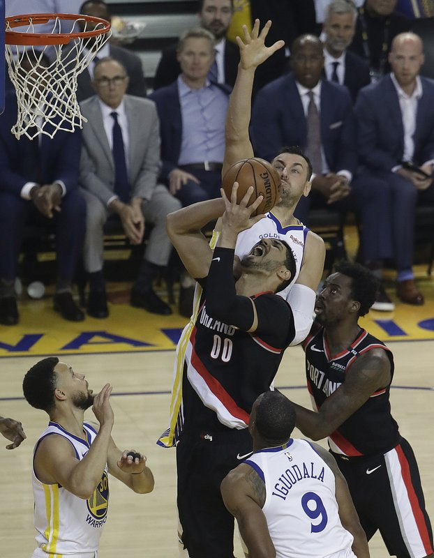 Portland Trail Blazers' Enes Kanter (00) shoots between Golden State Warriors' Andre Iguodala (9) and Stephen Curry, left, during the first half of Game 1 of the NBA basketball playoffs Western Conference finals Tuesday, May 14, 2019, in Oakland, Calif. (AP Photo/Jeff Chiu)