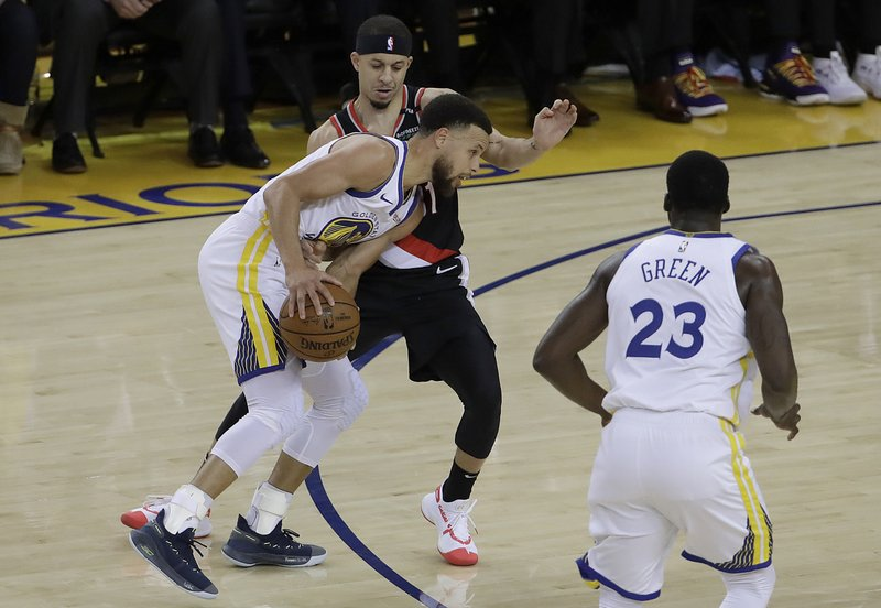 Golden State Warriors guard Stephen Curry, bottom left, is defended by Portland Trail Blazers guard Seth Curry during the first half of Game 1 of the NBA basketball playoffs Western Conference finals in Oakland, Calif. (AP Photo/Jeff Chiu)