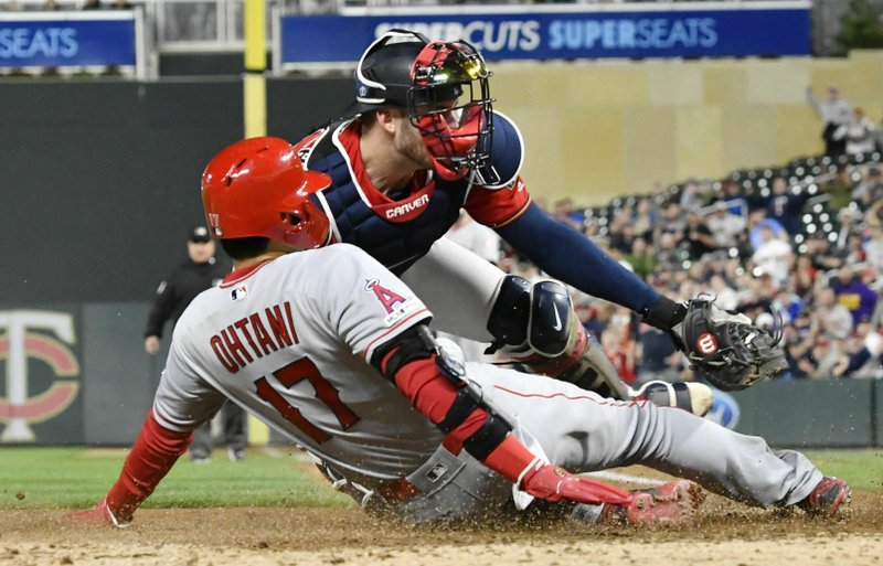 Minnesota Twins' catcher Mitch Garver, right, tags out Los Angeles Angels' Shohei Ohtani as he attempted to score from second base on a hit by Brian Goodwin in the eighth inning of a baseball game Tuesday, May 14, 2019, in Minneapolis. (AP Photo/Jim Mone)