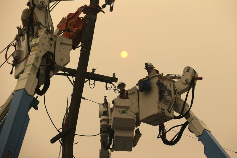 FILE - In this Nov. 9, 2018 file photo, Pacific Gas & Electric crews work to restore power lines in Paradise, Calif. (AP Photo/Rich Pedroncelli, File)