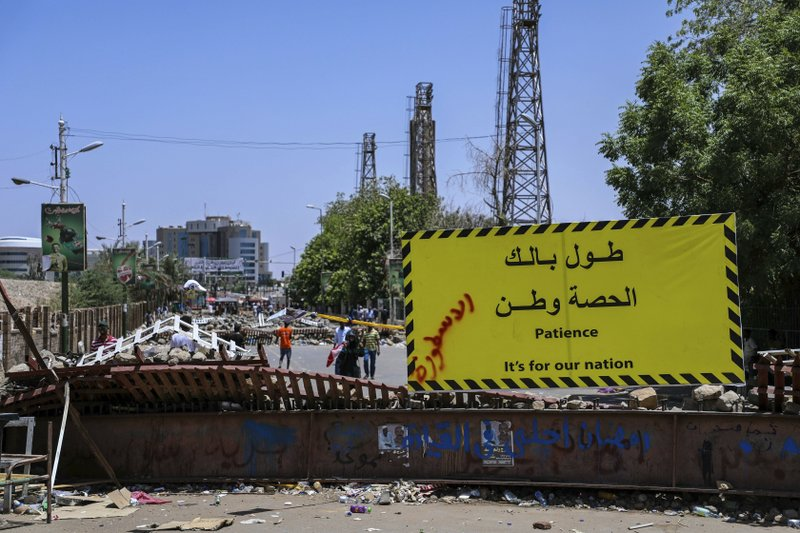 Protesters pass makeshift barricades on their way to the sit-in outside the Sudanese military headquarters, in Khartoum, Sudan, Tuesday, May 14, 2019. Sudanese protesters say security agents loyal to ousted President Omar al-Bashir attacked their sit-ins overnight, setting off clashes that left six people dead, including an army officer, and heightened tensions as the opposition holds talks with the ruling military council. Both the protesters and the transitional military council say the violence was instigated by al-Bashir loyalists from within the security forces. (AP Photo)