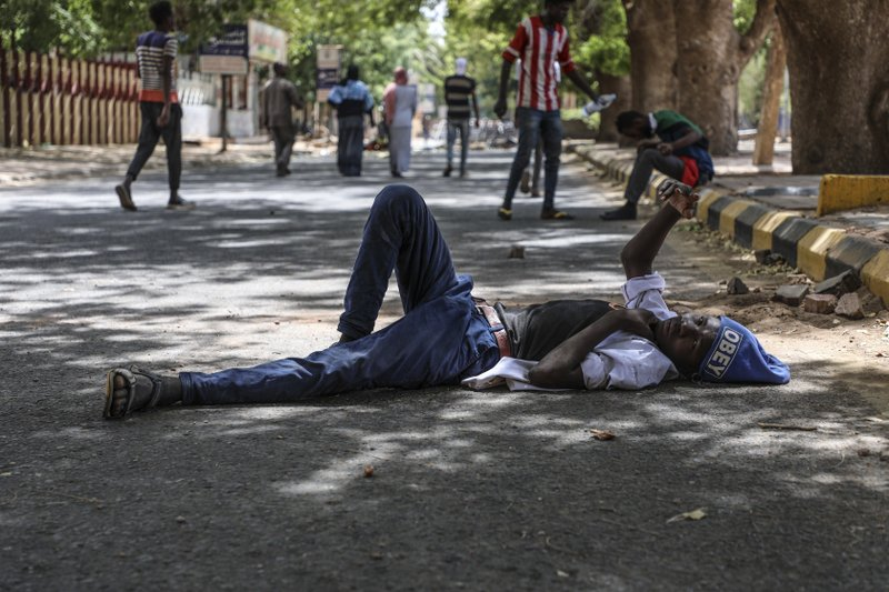 A protester takes a rest in a street leading to the sitin outside the Sudanese military headquarters, in Khartoum, Sudan, Tuesday, May 14, 2019. (AP Photo)