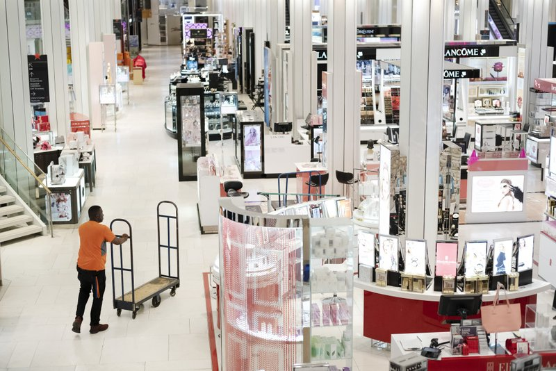 FILE - In this April 10, 2019, file photo a man pushes a stock cart through Macy's before the store opens to customers in New York. (AP Photo/Mark Lennihan, File)