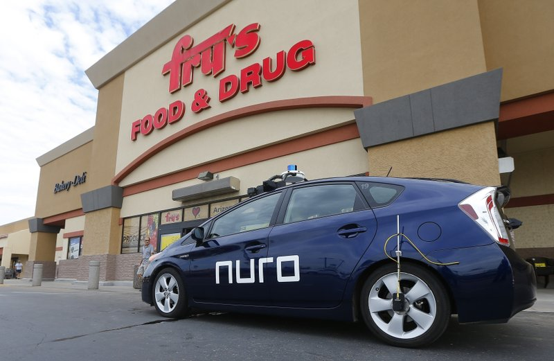 FILE - This Aug. 16, 2018, file photo shows a self-driving Nuro vehicle parked outside a Fry's supermarket, which is owned by Kroger, as part of a pilot program for grocery deliveries in Scottsdale, Ariz. (AP Photo/Ross D. Franklin, File)