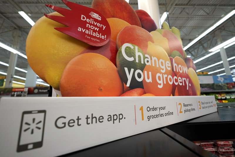 FILE- In this Nov. 9, 2018, file photo a sign promotes online and home delivery of groceries at a Walmart Supercenter in Houston. (AP Photo/David J. Phillip, File)