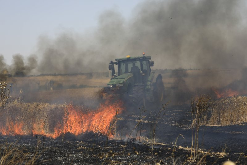 Israeli farmer battles fire started by an incendiary device launched from Gaza Strip, near the Israel and Gaza border fence, Wednesday, May 15, 2019. (AP Photo/Tsafrir Abayov)