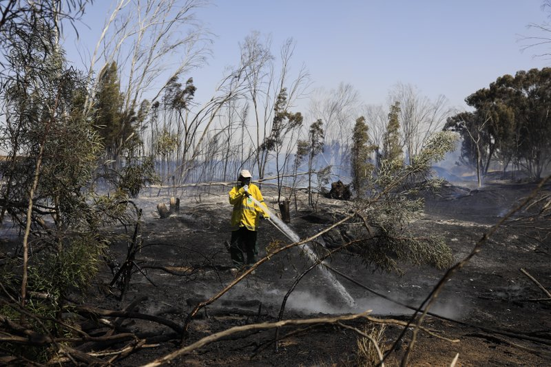 Israeli firefighter battles a fire started by an incendiary device launched from Gaza Strip, near the Israel and Gaza border fence, Wednesday, May 15, 2019. (AP Photo/Tsafrir Abayov)