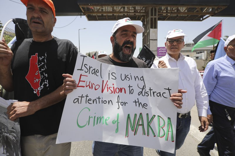 A man holds anti-Eurovision banner as Palestinian marked the 71st anniversary of their mass displacement during the 1948 war around Israel's creation. (AP Photo/Mahmoud Illean)
