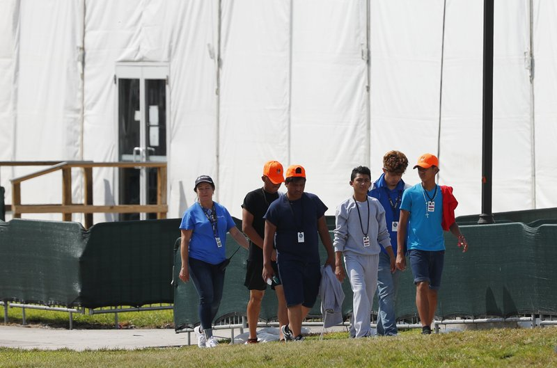 FILE - In this Monday, May 6, 2019 file photo, migrant children walk outside the Homestead Temporary Shelter for Unaccompanied Children in Homestead, Fla. (AP Photo/Wilfredo Lee, File)