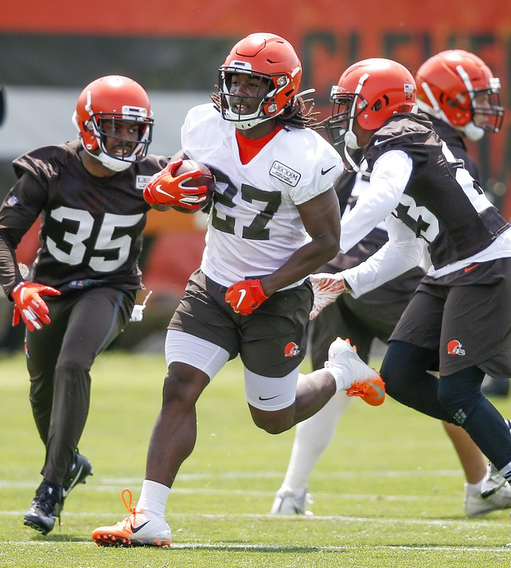 Cleveland Browns' Kareem Hunt (27) runs against Jermaine Whitehead (35) and Damarious Randall during an NFL football organized team activity session at the team's training facility Wednesday, May 15, 2019, in Berea, Ohio. (AP Photo/Ron Schwane)