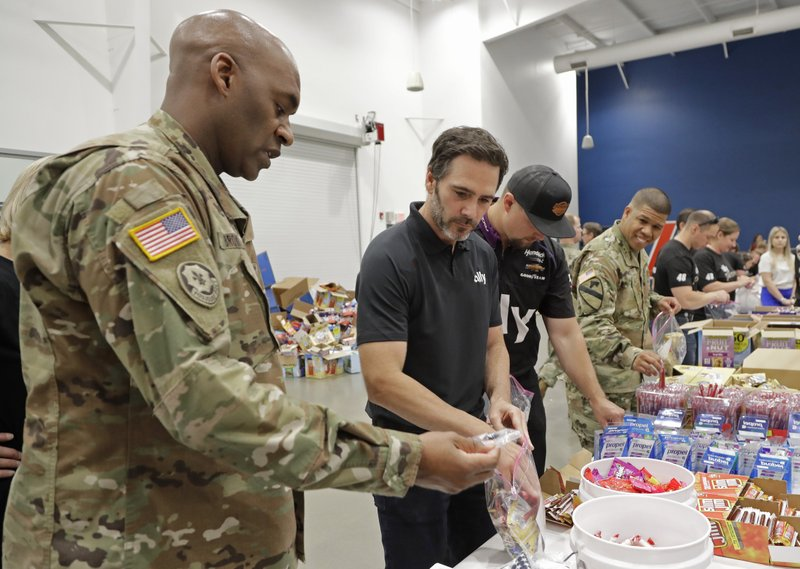 NASCAR driver Jimmie Johnson, second from left, helps assemble care packages for the North Carolina USO during a news conference in Concord, N. (AP Photo/Chuck Burton)