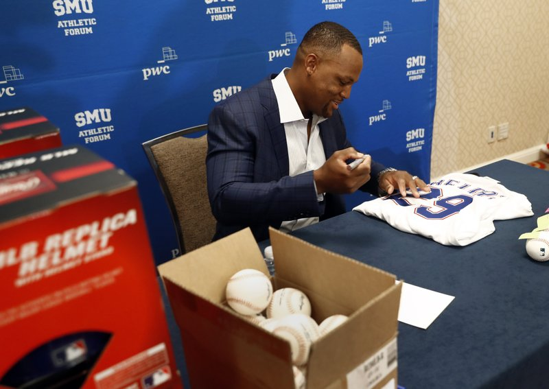 Adrian Beltre, retired MLB baseball player, autographs sports memorabilia before the start of a news conference during the SMU Athletic Forum in Dallas, Wednesday, May 15, 2019. (AP Photo/Tony Gutierrez)
