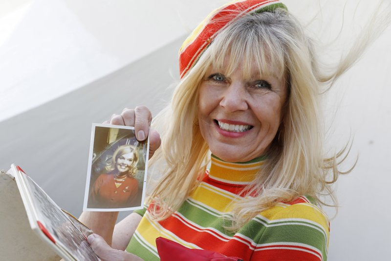 Susan Meekma Stevens holds a photo of herself when she was hired by TWA at the newly opened TWA Hotel at New York's John F. (AP Photo/Mark Lennihan)