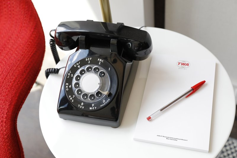 A vintage telephone and notepad are placed in a guest room for the opening of the TWA Hotel at New York's John F. (AP Photo/Mark Lennihan)