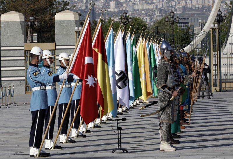 Members of military honour guard in historical costumes and holding 16 flags of old Turkish states wait for a welcome ceremony for Iraqi Prime Minister Adel Abdul-Mahdi shake hands during a welcome ceremony, in Ankara, Turkey, Wednesday, May 15, 2019.(AP Photo/Burhan Ozbilici)