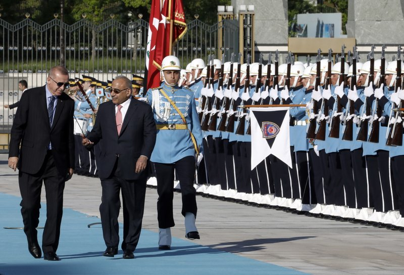 Turkish President Recep Tayyip Erdogan, left, and Iraqi Prime Minister Adel Abdul-Mahdi speak as they inspect an honour guard during a welcome ceremony, in Ankara, Turkey, Wednesday, May 15, 2019.(AP Photo/Burhan Ozbilici)
