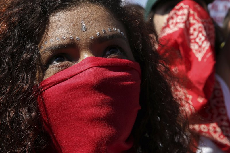 A masked student takes part in a nation-wide education strike, in Brasilia, Brazil, Wednesday, May 15, 2019. (AP Photo/Eraldo Peres)