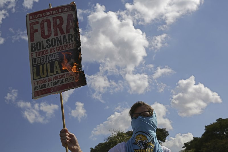 A masked student burns a poster with a message that reads in Portuguese: