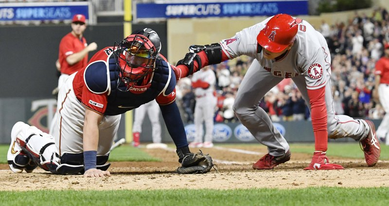 Los Angeles Angels' Shohei Ohtani, right, comes to the aid of Minnesota Twins' catcher Mitch Garver after Garver was injured tagging out Ohtani as he attempted to score from second base on a hit by Brian Goodwin in the eighth inning of a baseball game Tuesday, May 14, 2019, in Minneapolis. (AP Photo/Jim Mone)