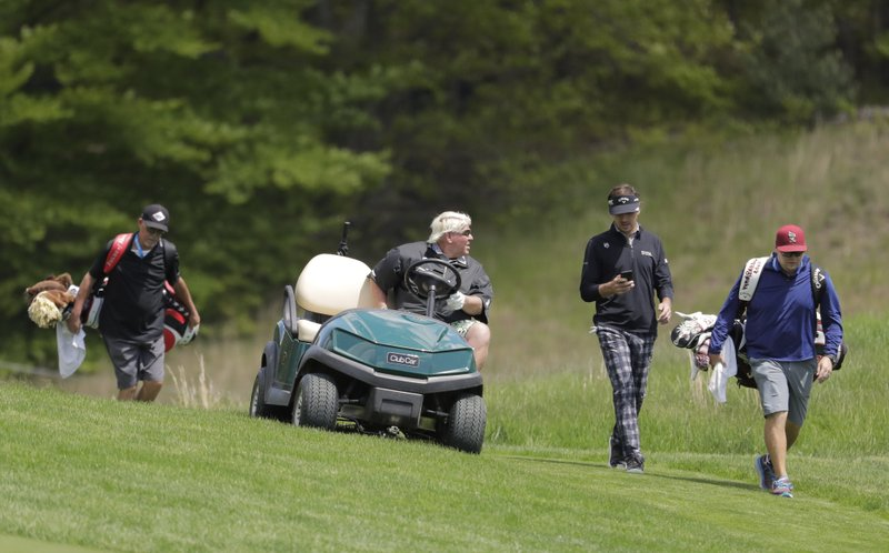 John Daly, second from left, talks with Kelly Kraft, second from right, as they move to the ninth fairway during a practice round for the PGA Championship golf tournament, Wednesday, May 15, 2019, at Bethpage Black in Farmingdale, N. (AP Photo/Julio Cortez)