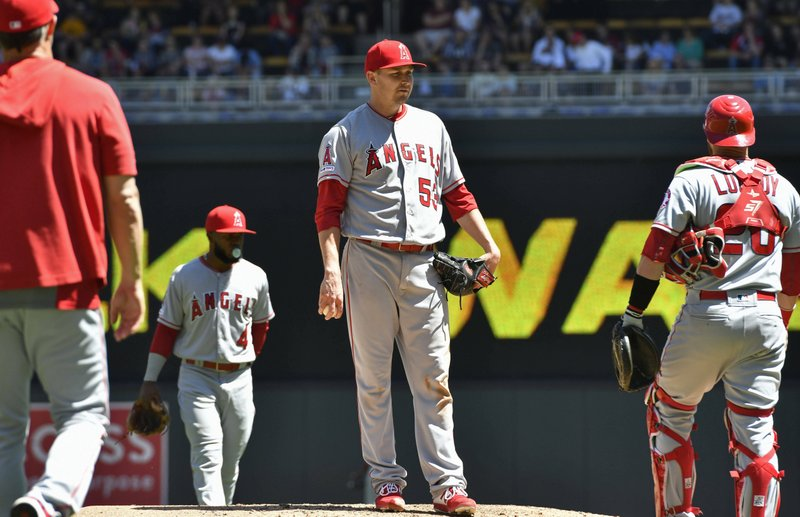 Los Angeles Angels pitcher Trevor Cahill, center, waits to be pulled by manager Brad Ausmus, left, after giving up a walk to Minnesota Twins' C. (AP Photo/Jim Mone)
