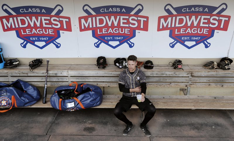 In this Monday, May 13, 2019 photo, Quad Cities River Bandits infielder Trey Dawson sits in the dugout before a Class-A Midwest League baseball game against the Cedar Rapids Kernels in Cedar Rapids, Iowa. (AP Photo/Charlie Neibergall)